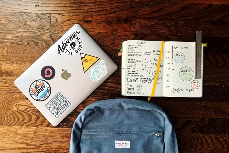 A laptop with stickers, a textbook with writing and diagrams and a blue backpack against a wood background
