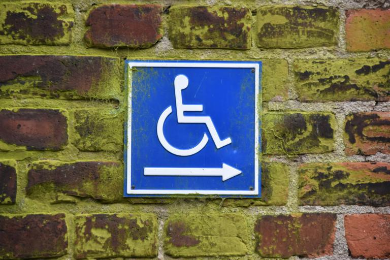 A blue and white wheelchair sign on a brick wall with an arrow pointing to the right