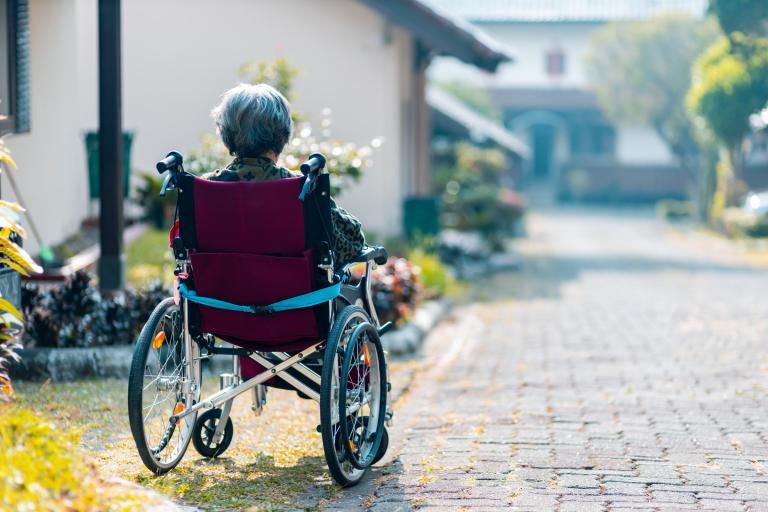 A lady in a wheelchair seen from behind with buildings in the background